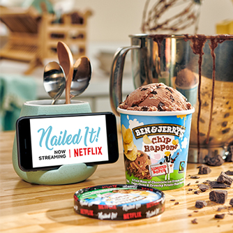 An open pint of Chip Happens ice cream next to a mobile phone displaying a title screen for Nailed It on Netflix